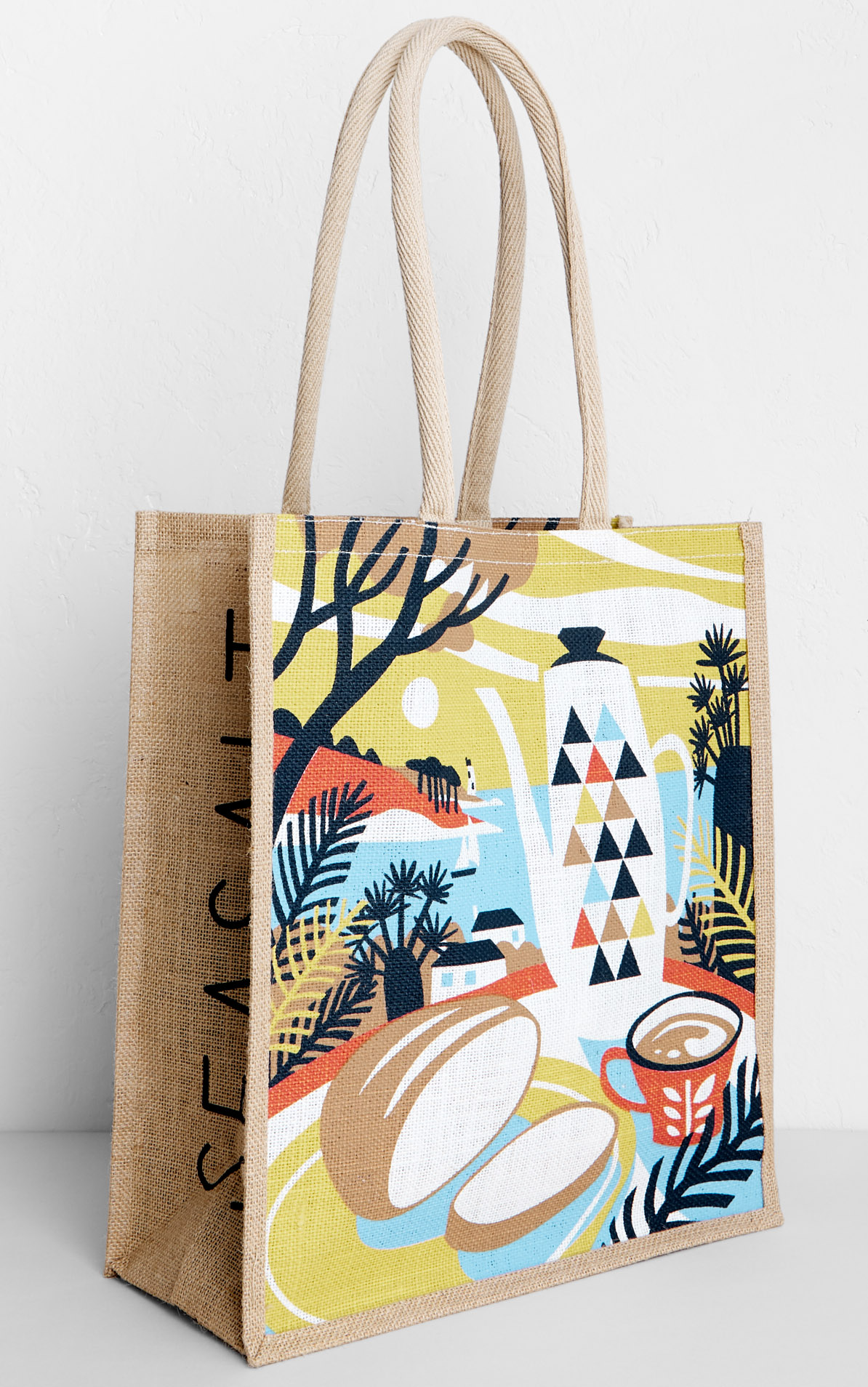 Jute bag with print design of bread loaf and mid-century coffee pot and cup, with tree ferns, pines and St Anthony's Head lighthouse in background. Inspired by a visit to Lamorran Gardens in St Mawes. By Matt Johnson for Seasalt Cornwall.